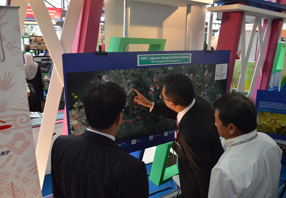 LOOKING CLOSELY - Dato' Abdul Rahman Dahlan (middle) studying the map of the MRT Sungai Buloh-Kajang alignment at the MRT Corp booth. With him is Datuk Wira Azhar Abdul Hamid (right).