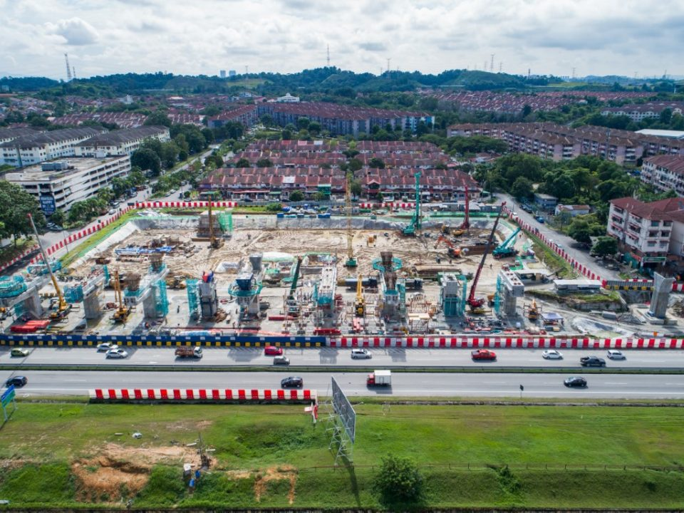 Pandangan udara pelancar segmen pratuang berbentuk T dan pembinaan cerucuk gerek dan tukup cerucuk untuk kemudahan tempat letak kereta bertingkat berhampiran tapak Stesen MRT Taman Equine.