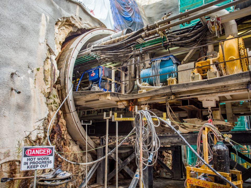 Pandangan mesin pengorek terowong keluar dari mata terowong di tapak Stesen MRT Chan Sow Lin.