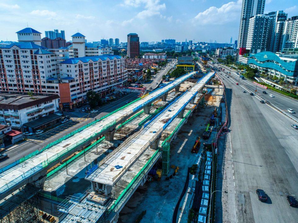 Pandangan udara tapak Stesen MRT Serdang Raya Utara menunjukkan kerja-kerja pembinaan galang kekotak bersegmen dan pelarasan rentang.