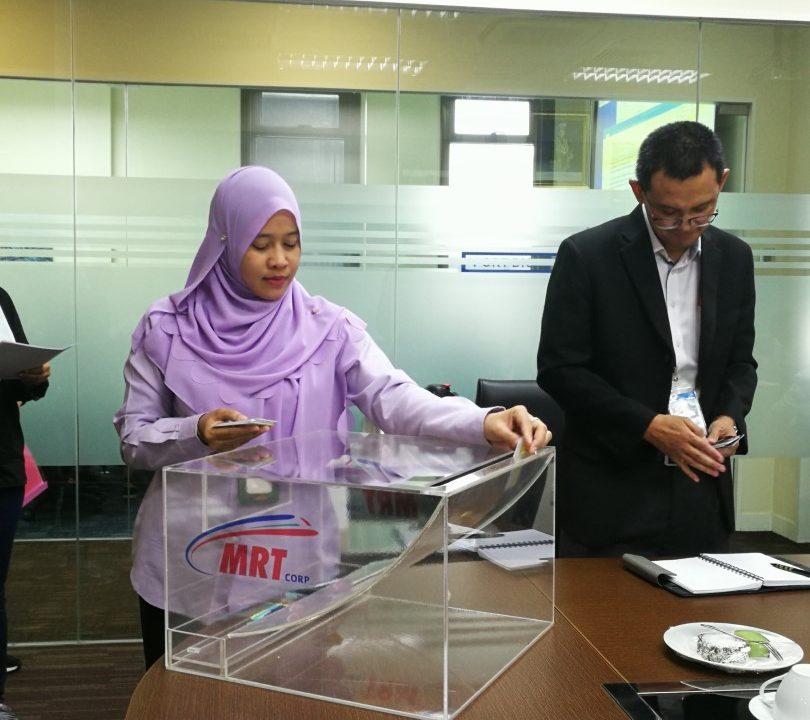 CABUTAN: Cik Ramzahidah dari MMC Gamuda KVMRT (PDP SSP) Sdn Bhd memasukkan nama ke dalam kotak undi semasa Cabutan Undian Bumiputera MRT Laluan Sungai Buloh-Serdang-Putrajaya yang ke-24.