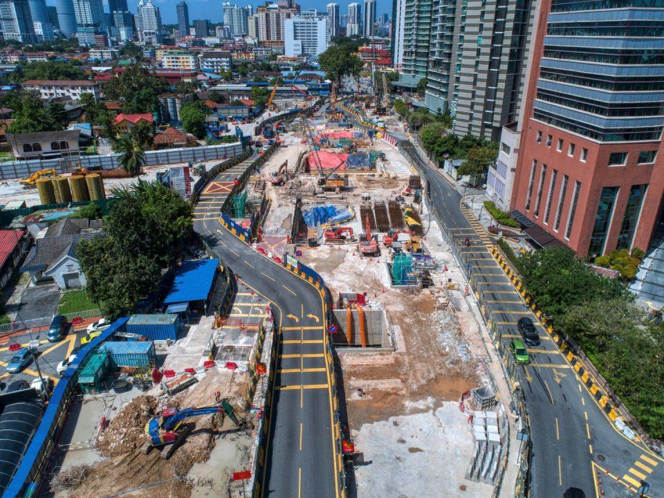 Pandangan udara tapak Stesen MRT Raja Uda menunjukkan kerja-kerja konkrit tetulang dan penggalian sedang dijalankan.