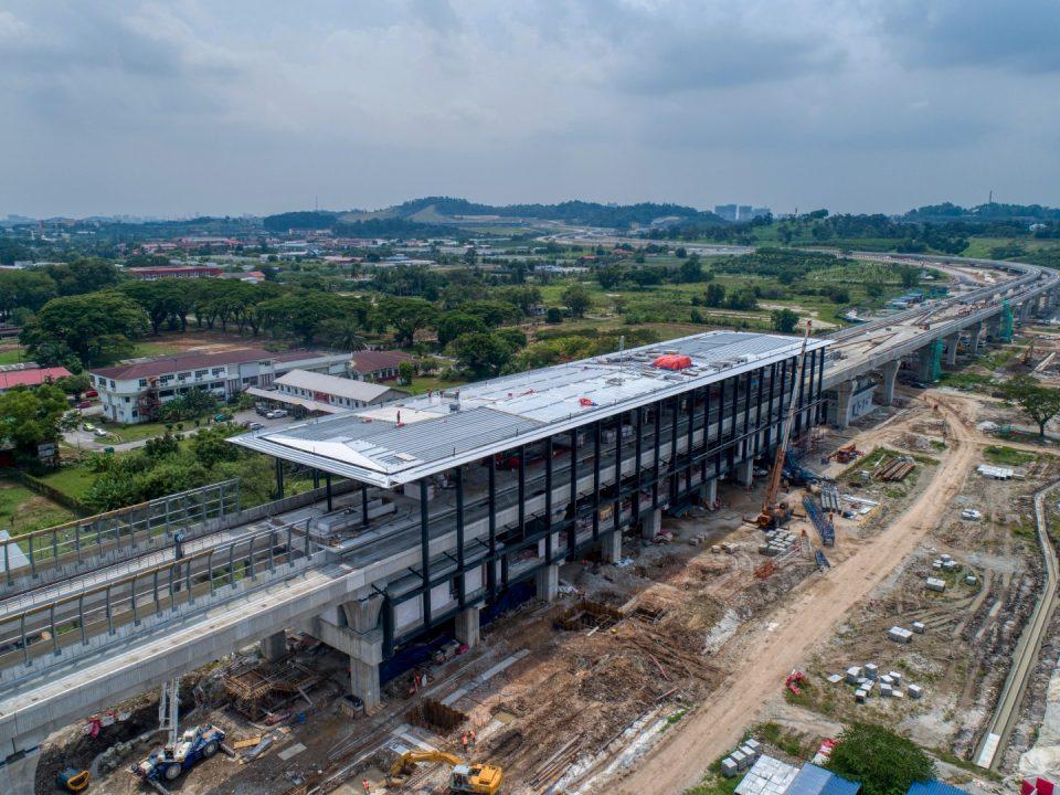 Pandangan udara tapak Stesen MRT UPM menunjukkan pemasangan kekuda bumbung dan struktur besi sedang dijalankan.