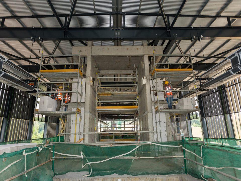 Tembok bata untuk kemasan seni bina bagi sokong penaik bersebelahan teras lif sedang dijalankan di aras platform Stesen MRT Taman Naga Emas