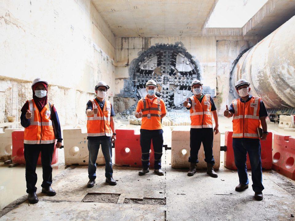 BERJAYA: Delegasi DanaInfra Nasional Berhad, Puan Zaniffa Azzura Abdullah (kiri), Encik Adi Johan Ab Wahab (kedua dari kiri) dan Encik Asri Ahmad (kanan), bergambar di hadapan penembusan Mesin Pengorek Terowong yang berjaya di Portal Selatan dengan Ketua Terowong Bawah Tanah, Encik Alexander William Terry (tengah) dan Ketua Pegawai Kewangan, Encik Shahrul Fadli Omar (kedua dari kanan)