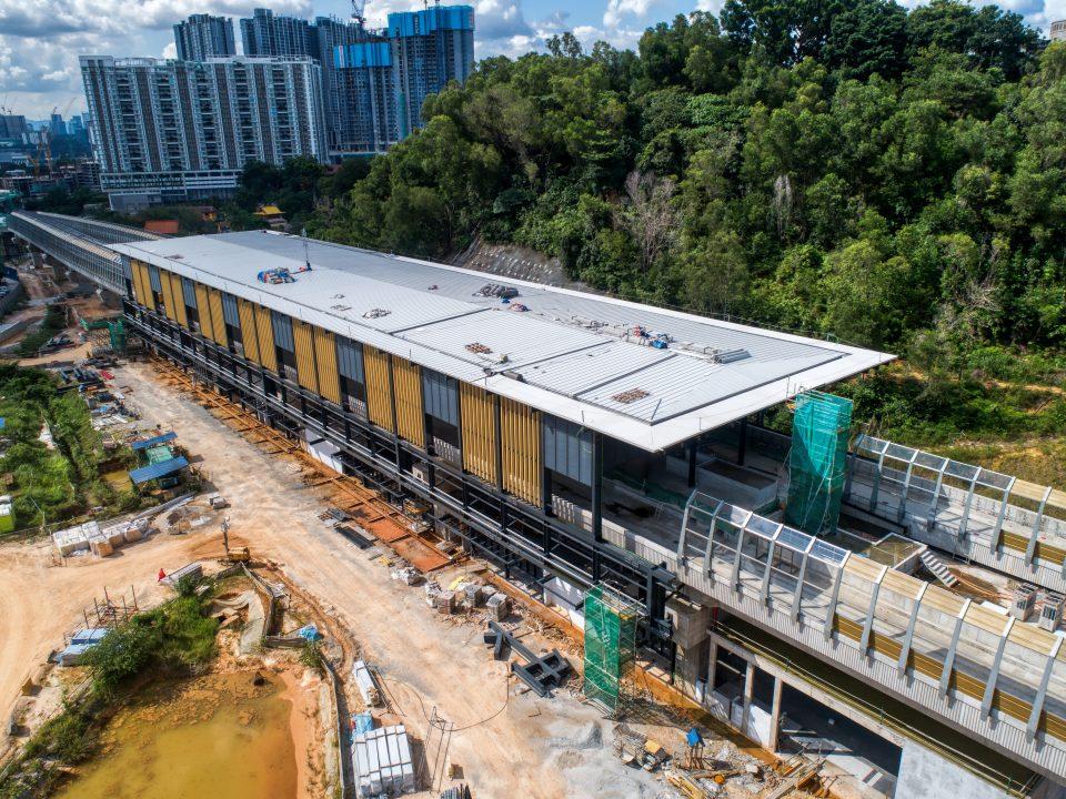 Pandangan udara tapak Stesen MRT Taman Naga Emas menunjukkan pemasangan fakad dan kerja-kerja pemasangan kepingan bumbung sedang dijalankan.
