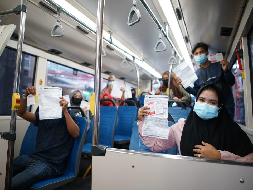 DIVAKSINASI: Penduduk PPR Lembah Subang menunjukkan bukti vaksinasi mereka semasa perjalanan pulang ke kediaman mereka menaiki Bas Perantara MRT Laluan Putrajaya